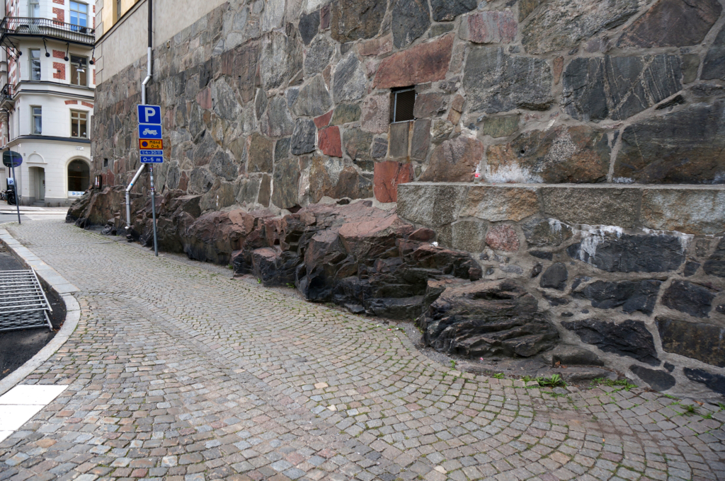 Rocky outcrop from the base of the foundation of a building in Stockholm. Two minutes before the photo was taken a man was resting on one to the irregular ledges. 2014. Photo by Xin Cheng